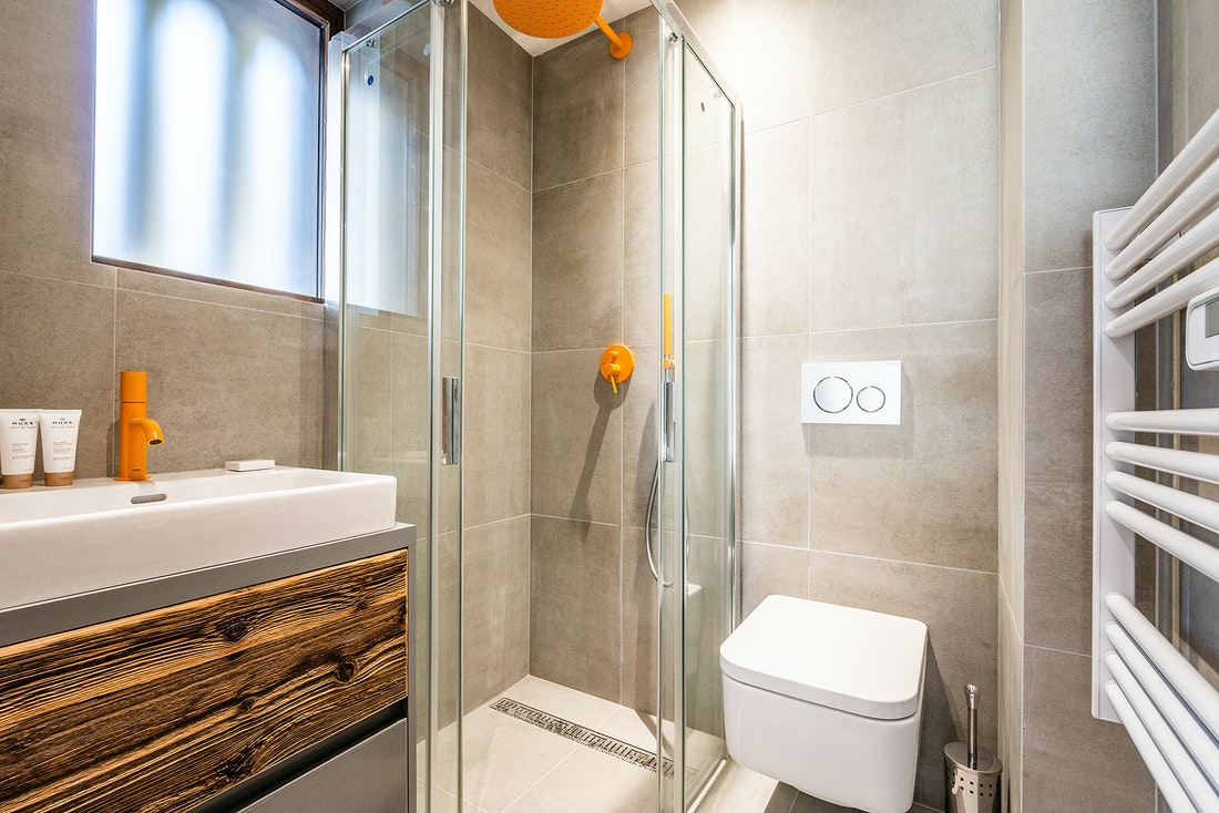 Modern bathroom with orange details Modern black and wooden kitchen at Eyong accommodation in Chamonix