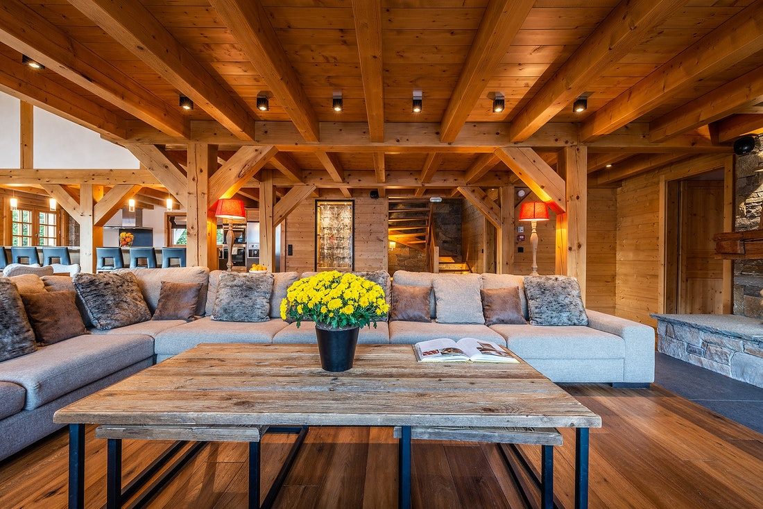 Couch and a wooden table in Abachi luxury chalet in Les Gets