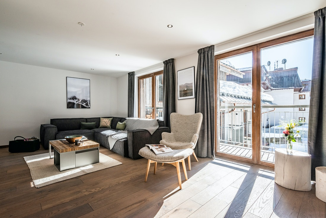 Living room with large grey couch at Badi luxury chalet in Chamonix