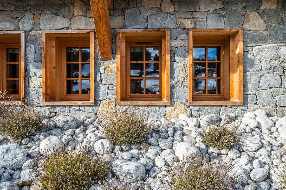 Wooden windows and stone walls of Abachi luxury chalet in Les Gets