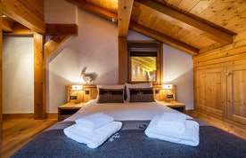 Queen size bed in the bedroom of Abachi luxury chalet in Les Gets