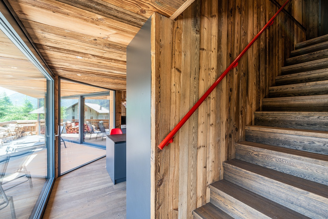 Wooden stairs and red railing at Le Rouge luxury chalet in Morzine