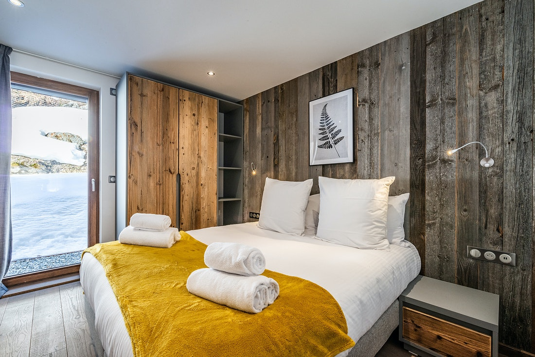 Bedroom with wooden walls and yellow details at Eyong accommodation in Chamonix