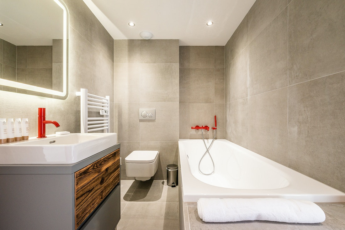 Bathroom with bathtub and red details at Ruby luxury accommodation in Chamonix