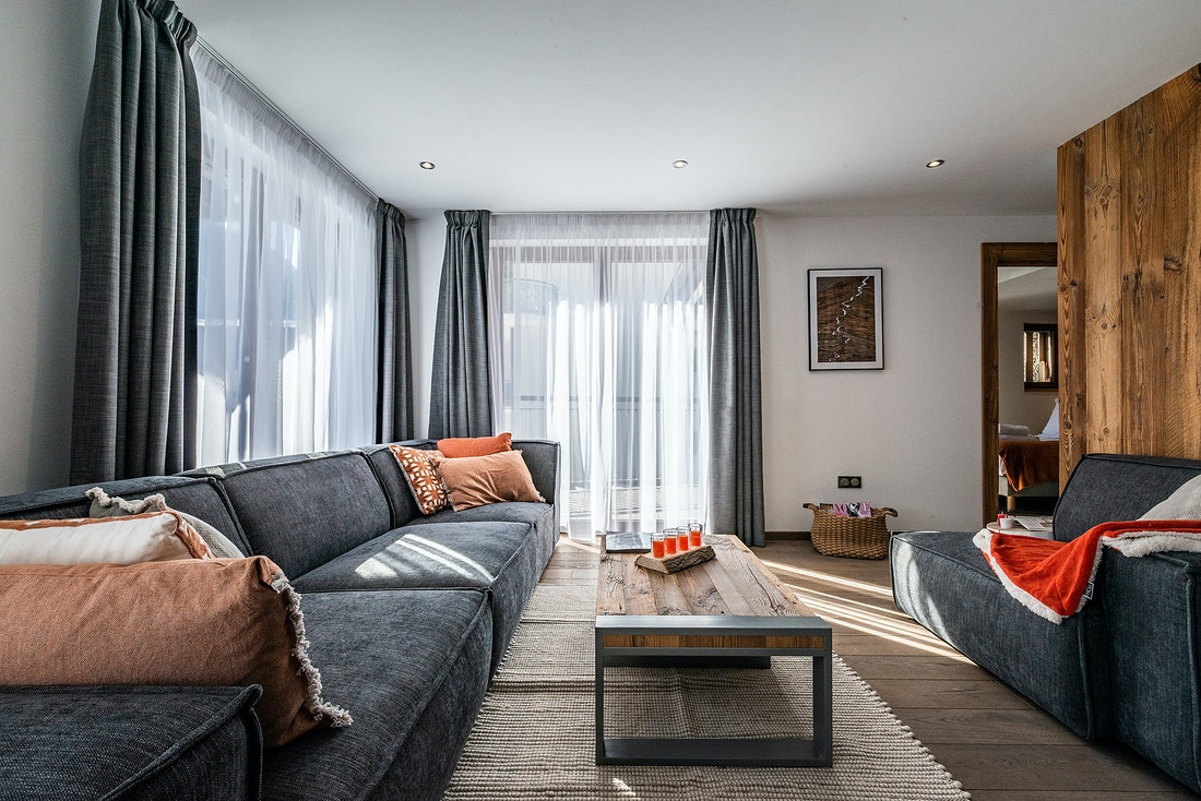 Living room with grey couch and orange pillows at Ravanel luxury accommodation in Chamonix