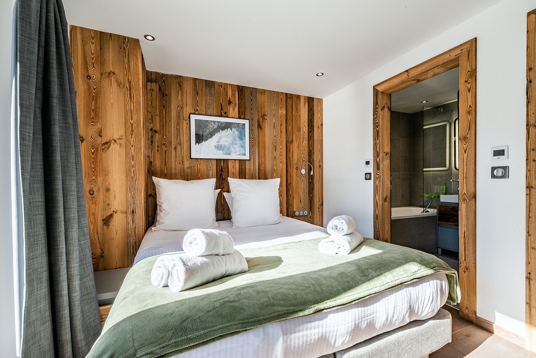 Double bedroom ensuite with green throw at Badi luxury chalet in Chamonix