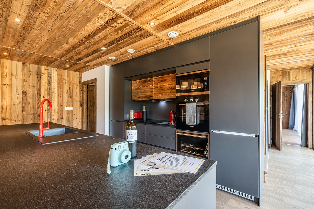 Black kitchen with a light blue polaroid at Le Rouge luxury chalet in Morzine