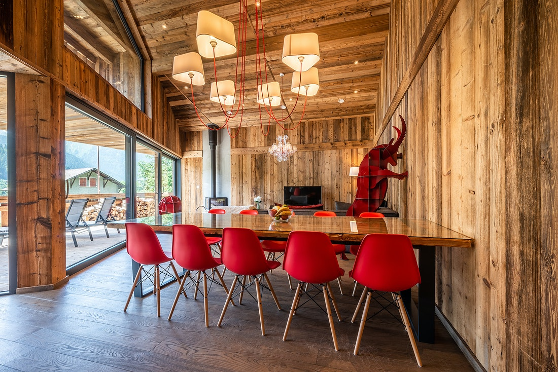 Large wooden dining table with red chairs at Le Rouge luxury chalet in Morzine