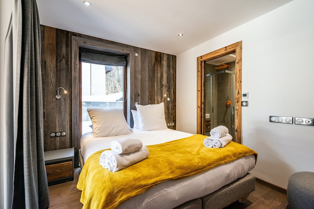 Double bedroom en-suite with a yellow throw Modern black and wooden kitchen at Eyong accommodation in Chamonix