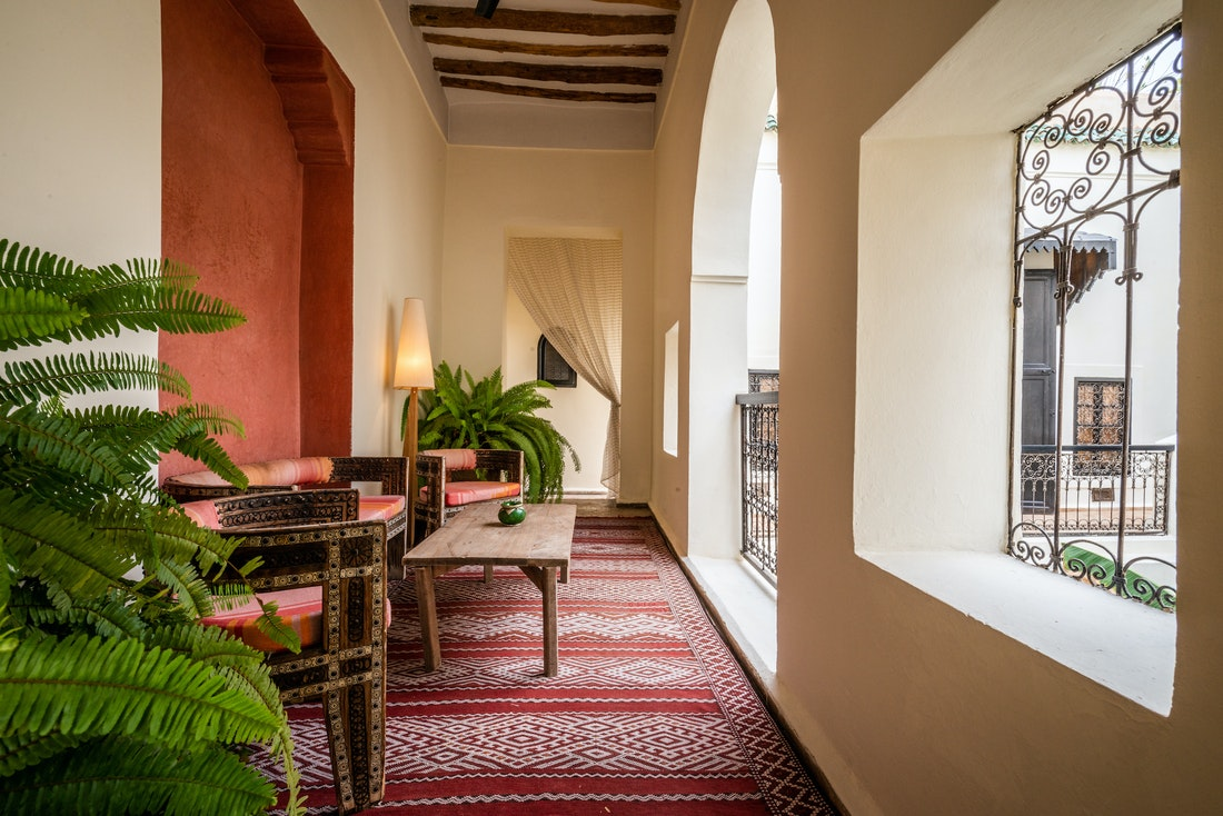 Outside covered seating area featuring a red and white berber rug at Adilah riad in Marrakech