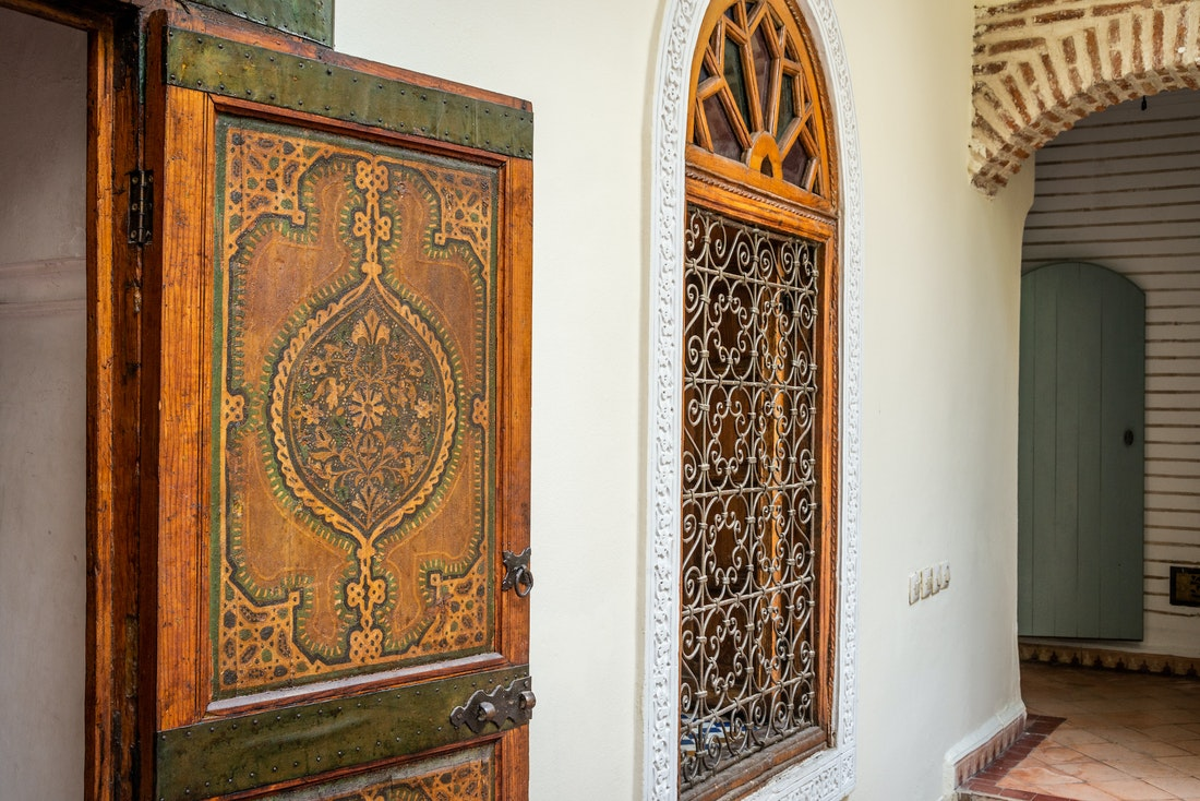 Traditional moroccan wooden door with paintings at Adilah riad in Marrakech