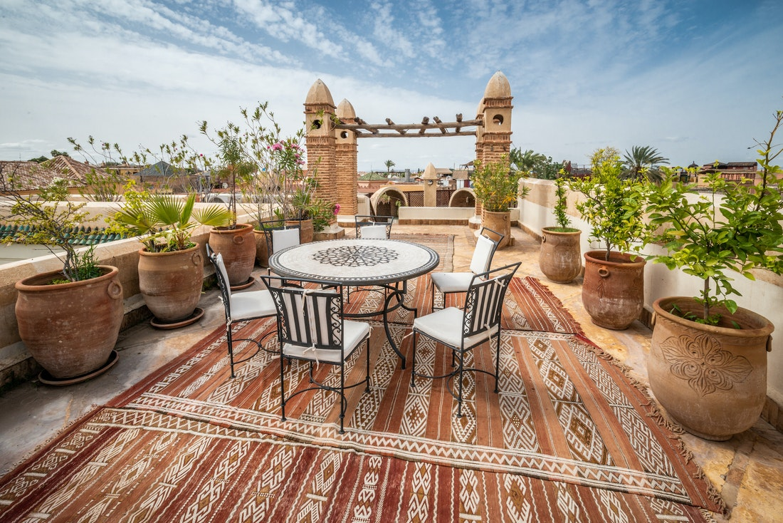 Rooftop terrace with table and chairs at Adilah riad in Marrakech
