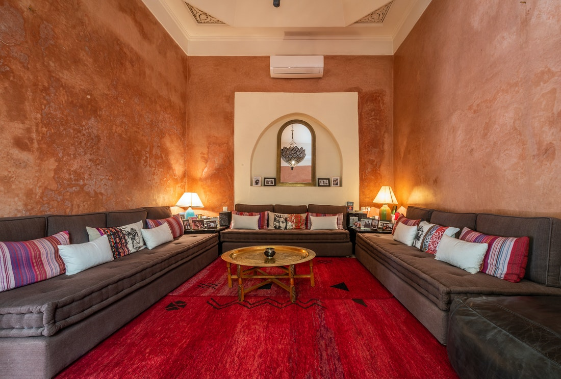 Lounge are with three large brown couches and a red berber rug at Adilah riad in Marrakech