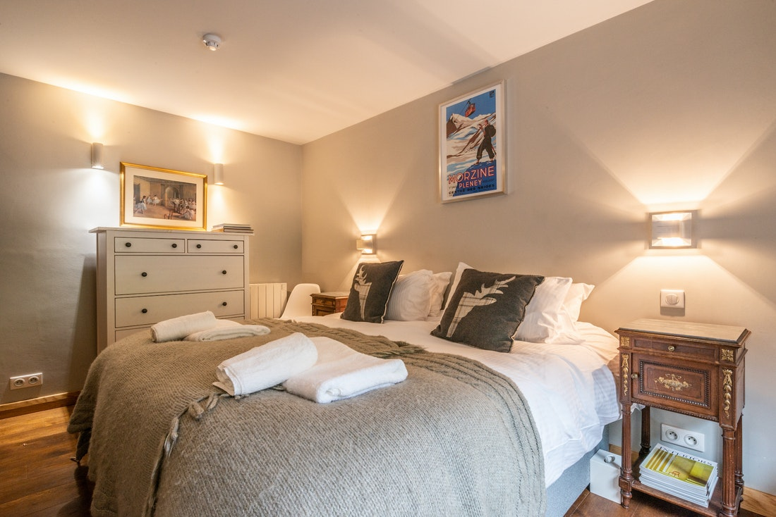 Double bedroom with vintage skiing poster at La Ferme de Margot luxury chalet in Morzine