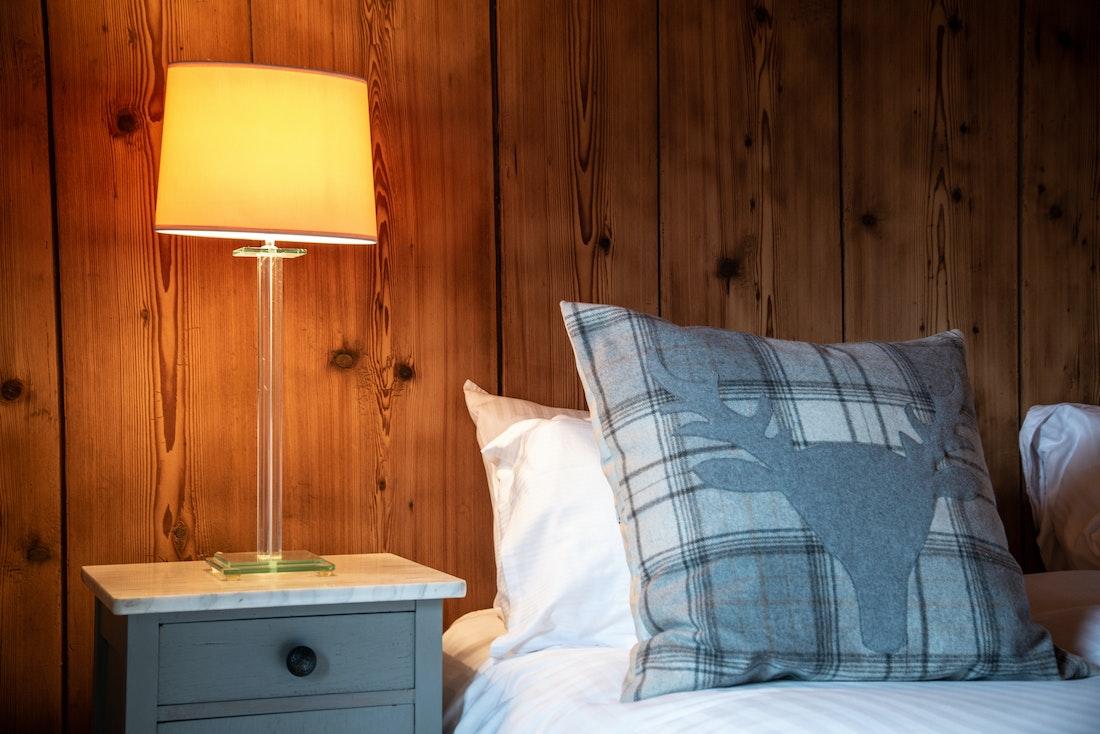 Bedside table with wooden wall at La Ferme de Margot luxury chalet in Morzine