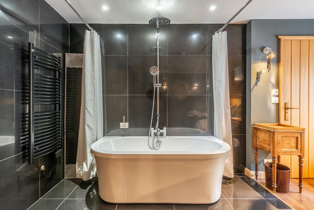 Black modern bathroom with bathtub at La Ferme de Margot luxury chalet in Morzine