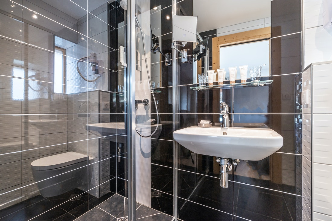 Black and white modern bathroom with shower at Ourson accommodation in Morzine