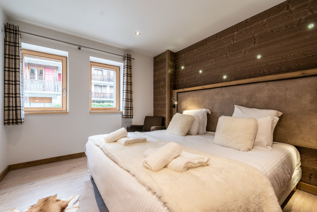 Double bedroom with faux-fur blanket and pillows at Ourson accommodation in Morzine