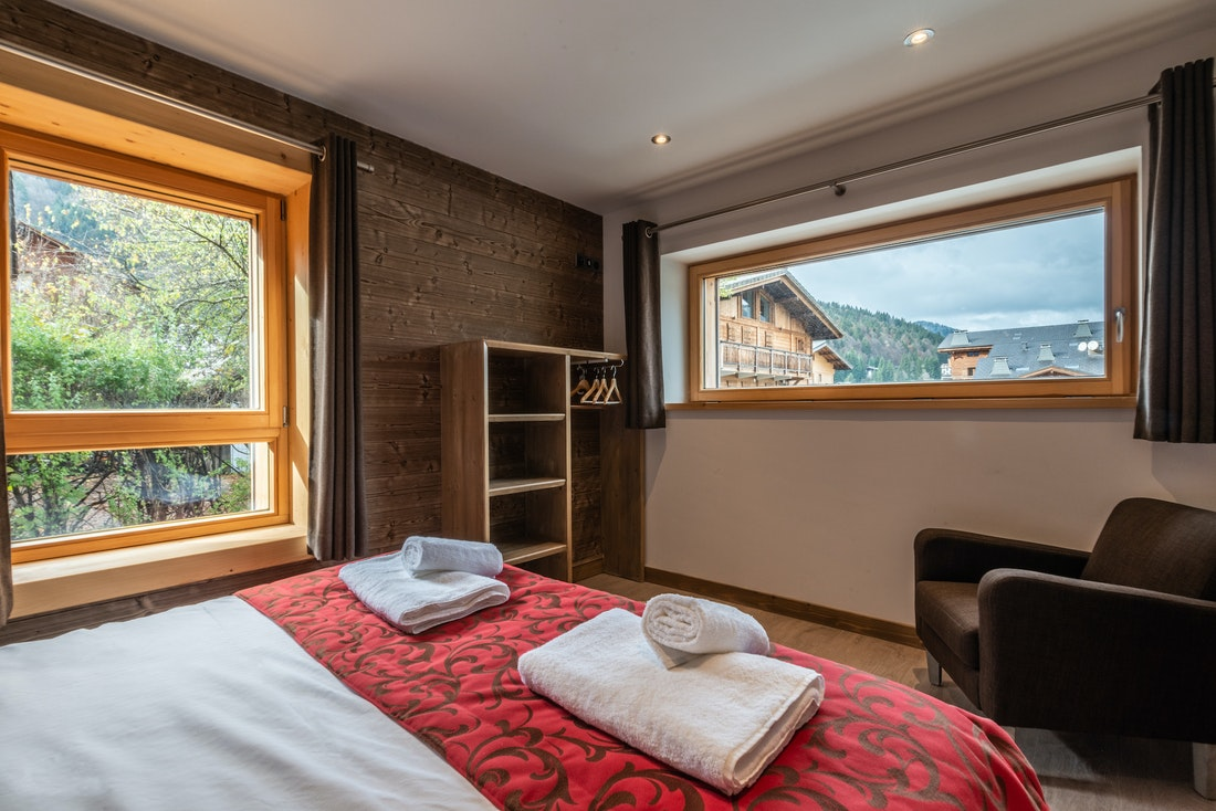 Double bedroom with wooden walls at Flocon accommodation in Morzine