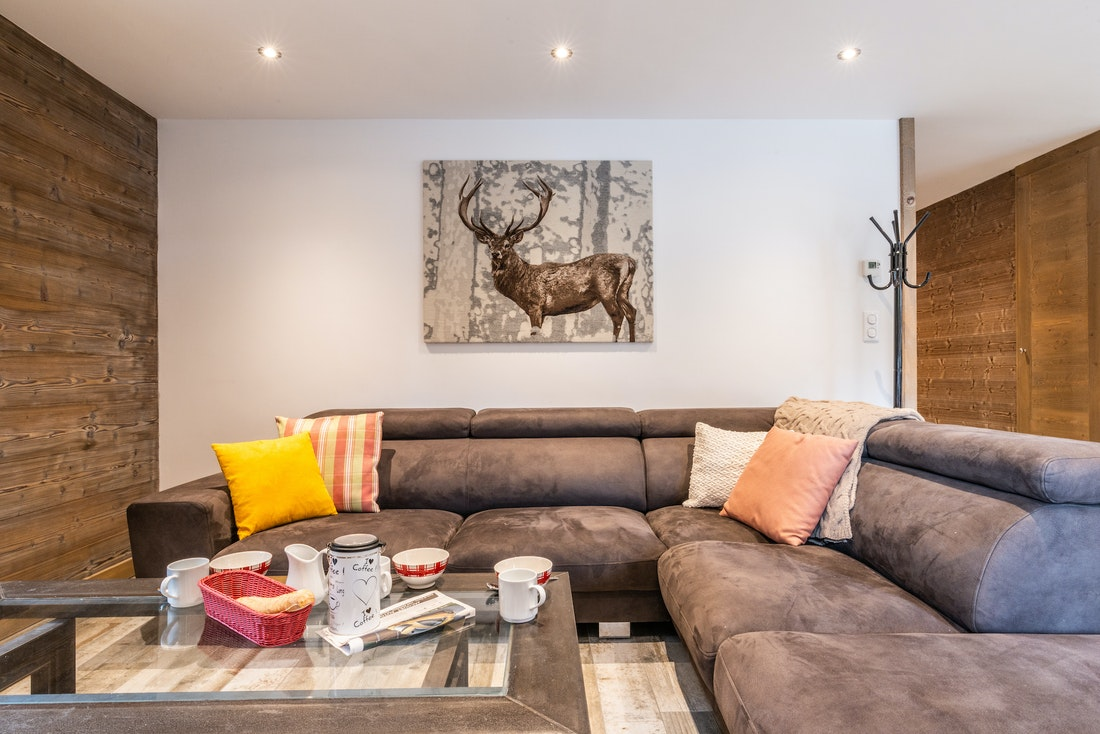 Living room with grey couch and transparent coffee table at Ourson accommodation in Morzine