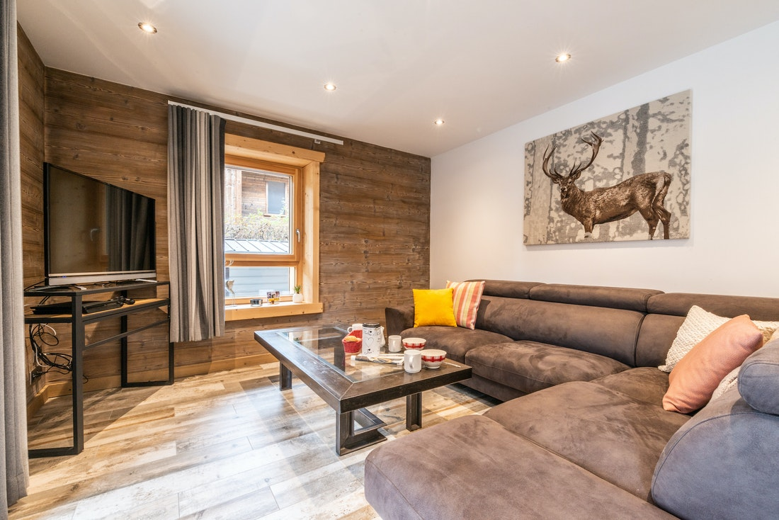Modern living room with dark grey couches and a TV at Flocon accommodation in Morzine