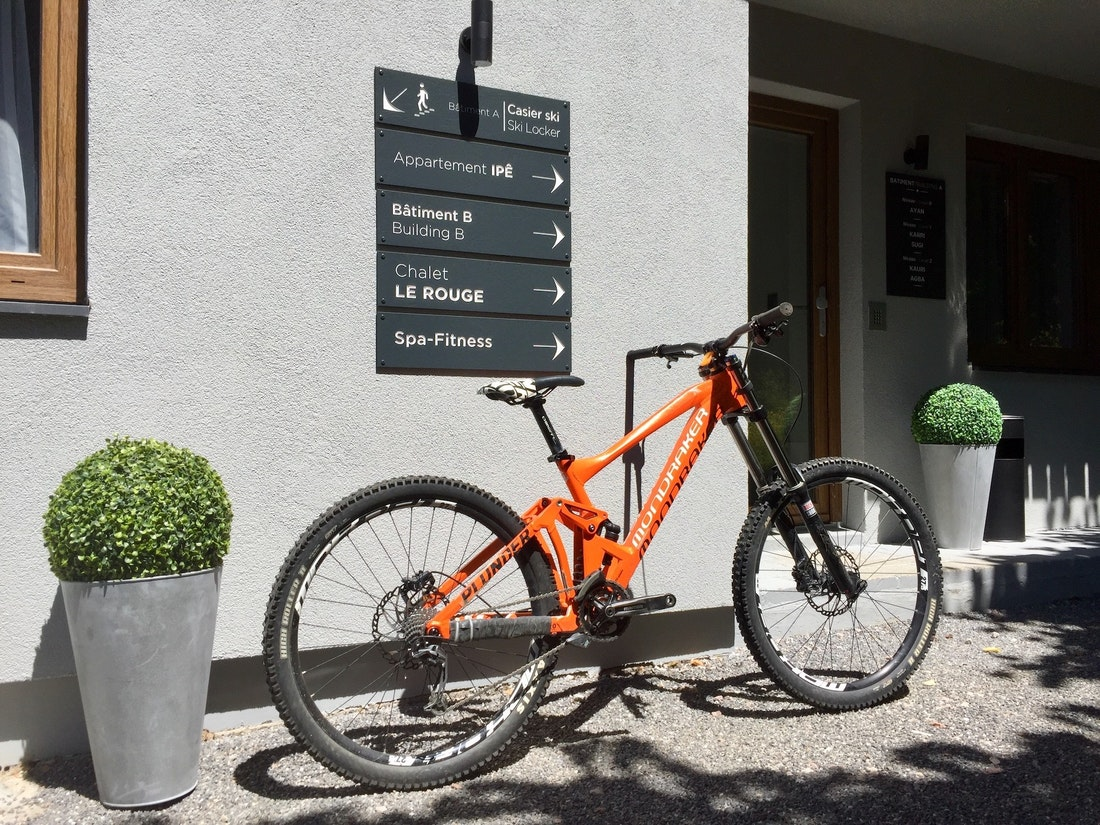Orange mountain bike in front of a ski apartment