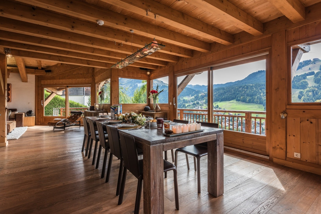 Large wooden dining table with views over the Alps at Omaroo I luxury chalet in Morzine