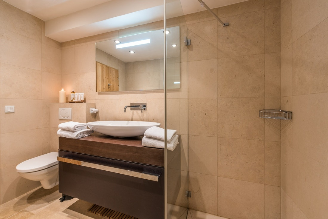 Beige and wooden bathroom with shower at Omaroo I luxury chalet in Morzine