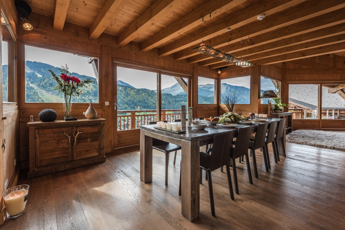 Wooden dining table with views over the Alps at Omaroo I luxury chalet in Morzine