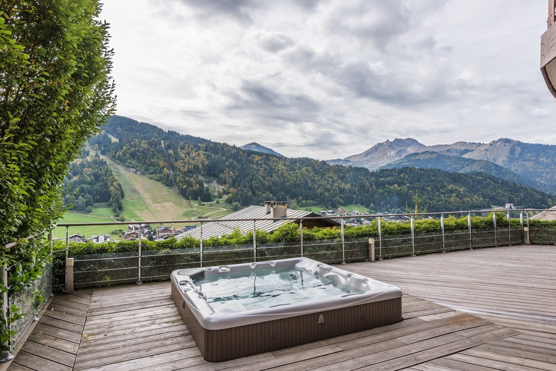Outdoor hot tub with views over the Alps at Omaroo I luxury chalet in Morzine