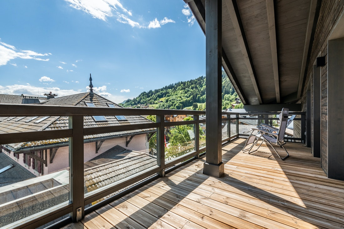 Wooden terrace with views over the alpine forest at Ozigo accommodation in Les Gets