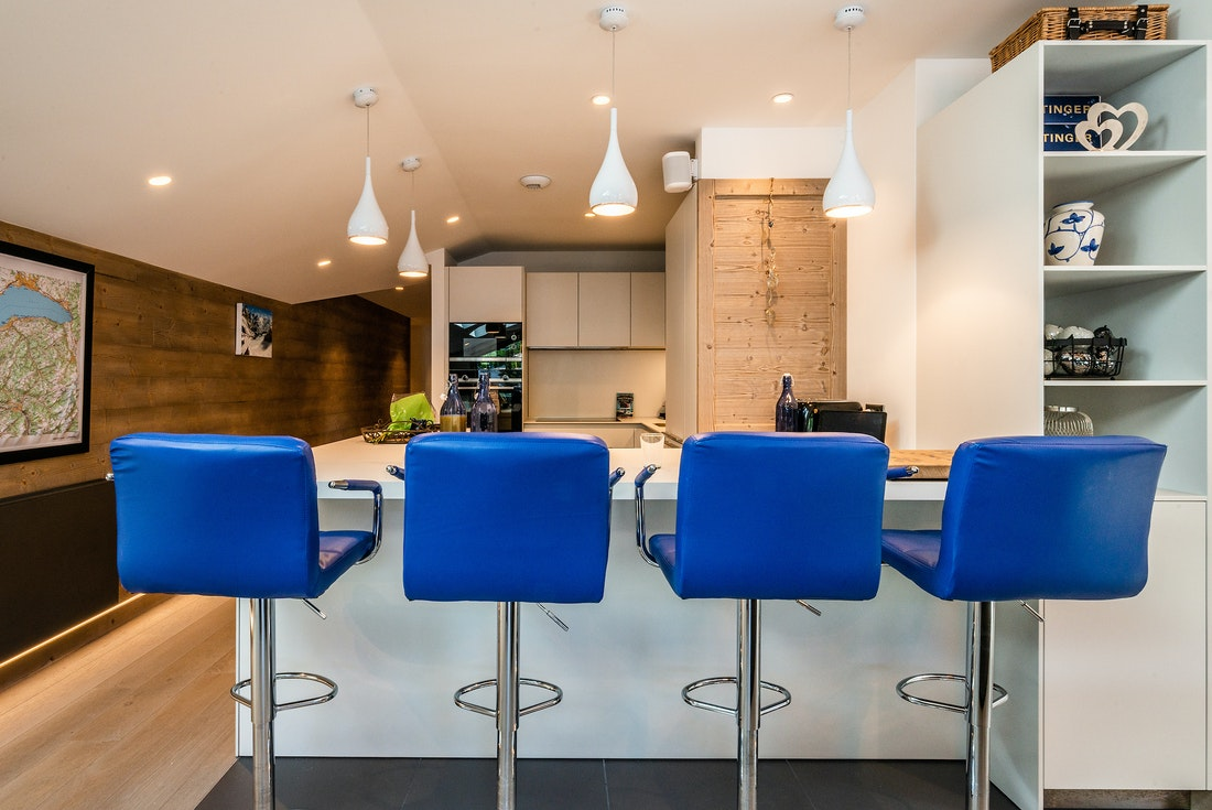 Open kitchen with high blue chairs at Ozigo accommodation in Les Gets