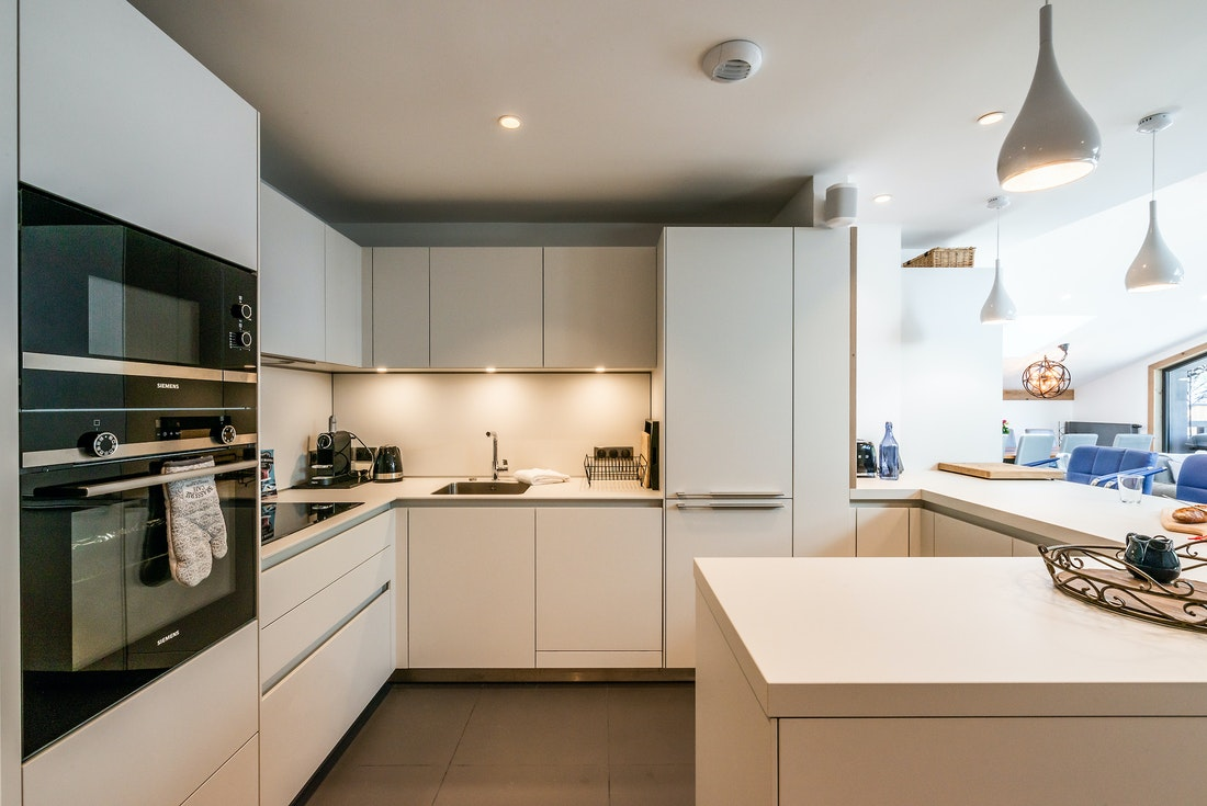 Fully-equipped white kitchen with blue chairs at Ozigo accommodation in Les Gets