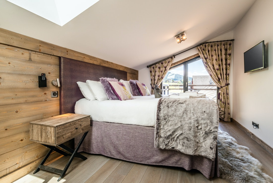 Ensuite Bedroom with wooden walls and television at Ozigo accommodation in Les Gets