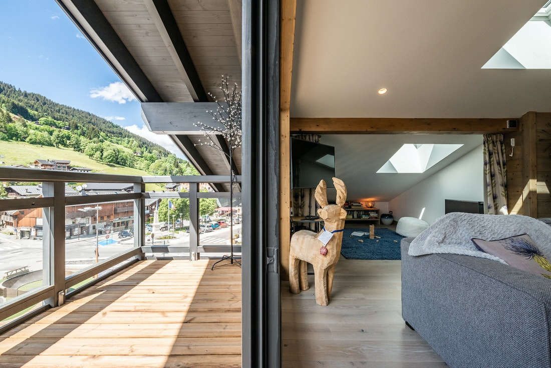Wooden terrace with large bay window at Ozigo accommodation in Les Gets