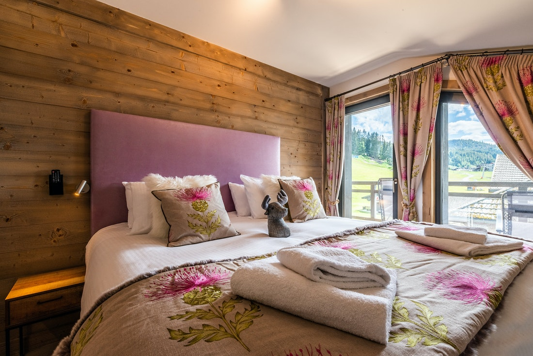 Ensuite Bedroom with wooden walls and colourful pillows at Ozigo accommodation in Les Gets