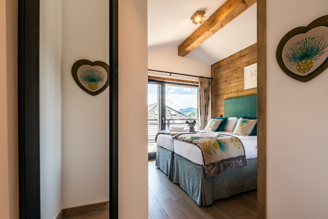 Ensuite Bedroom with wooden details and turquoise linens at Ozigo accommodation in Les Gets