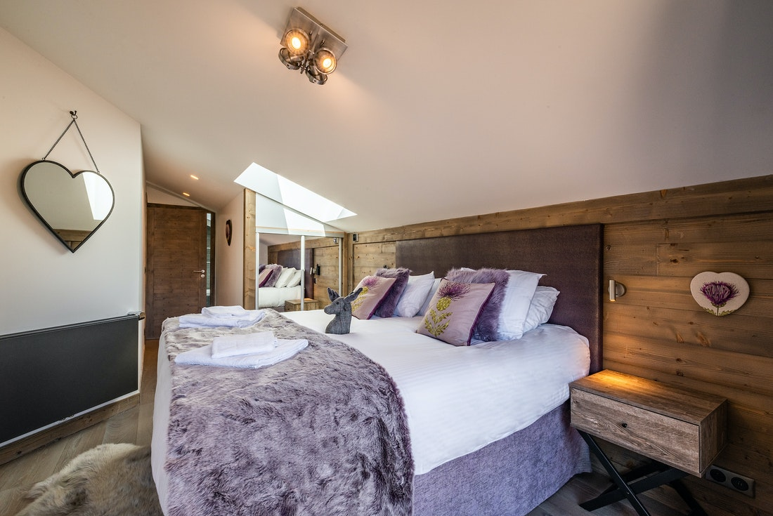 Ensuite Bedroom with heart-shaped mirror and purple linens at Ozigo accommodation in Les Gets