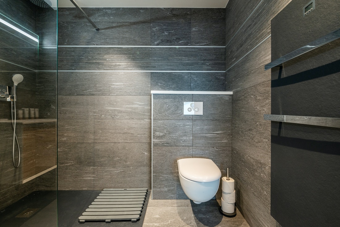 Modern bathroom with grey tiles and shower at Ozigo accommodation in Les Gets