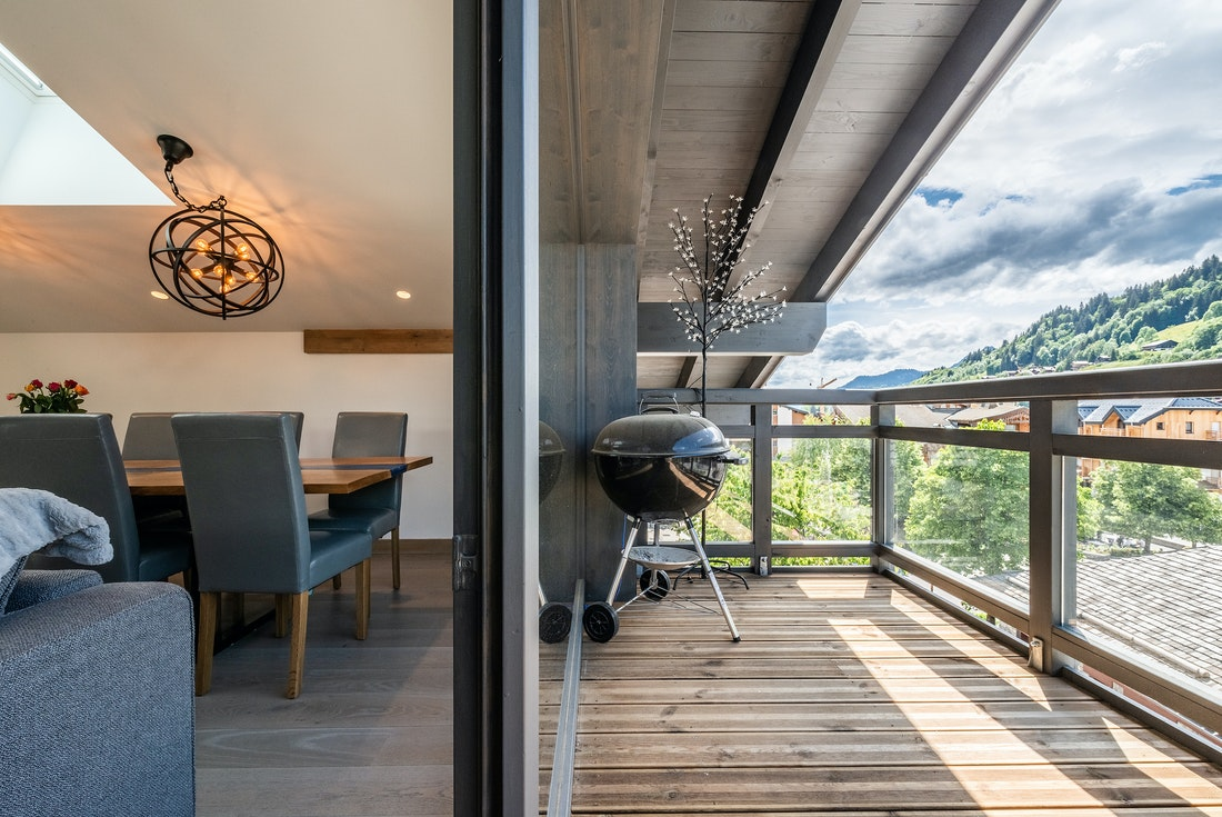 Wooden terrace with mountain views and bbq at Ozigo accommodation in Les Gets
