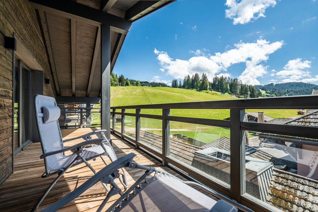 Wooden terrace overlooking the mountains with sun beds at Ozigo accommodation in Les Gets