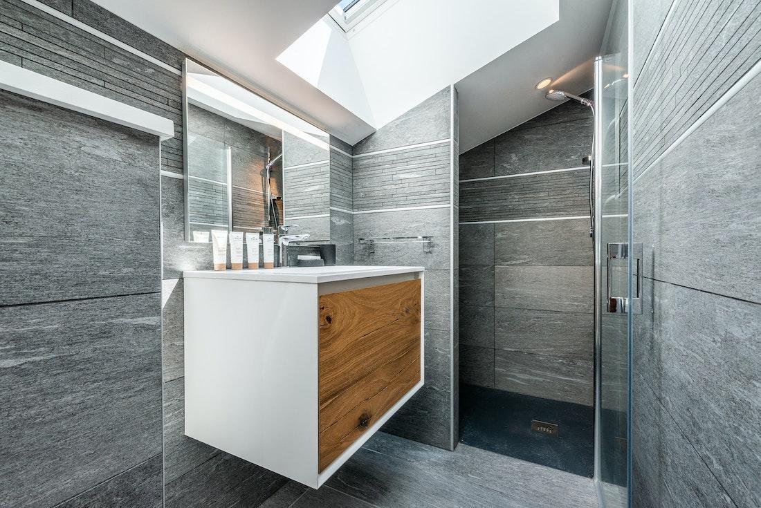 Modern grey bathroom with ceiling window at Ozigo accommodation in Les Gets