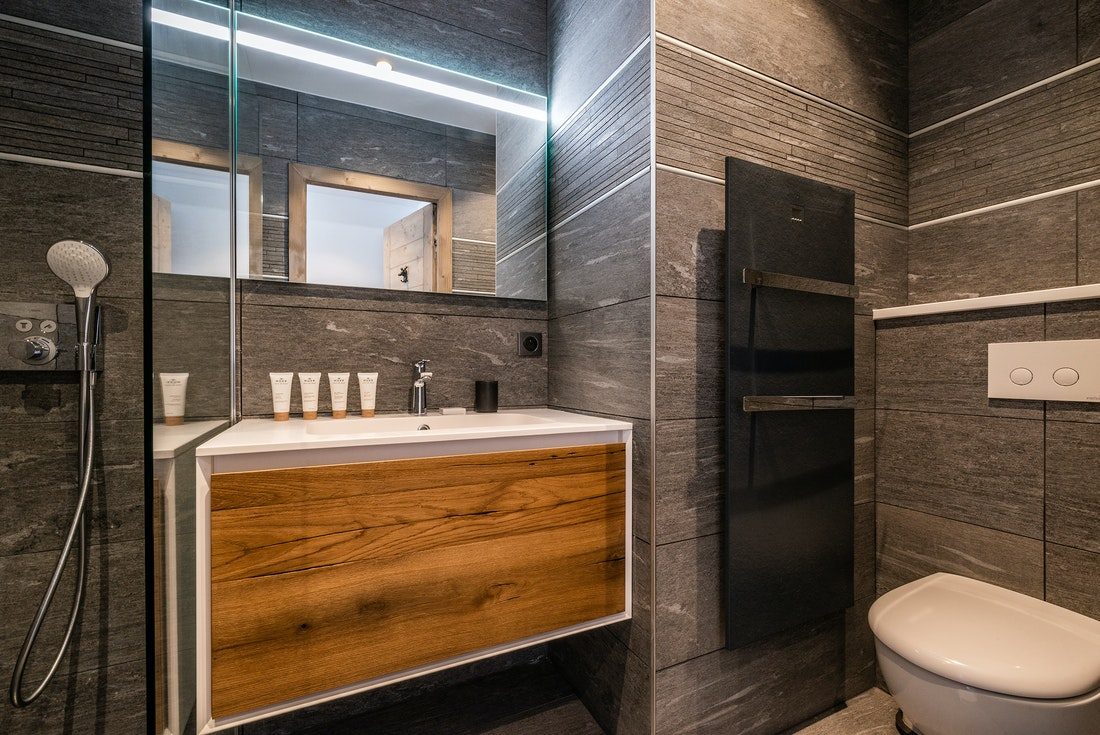 Modern bathroom with wooden sink and shower at Ozigo accommodation in Les Gets