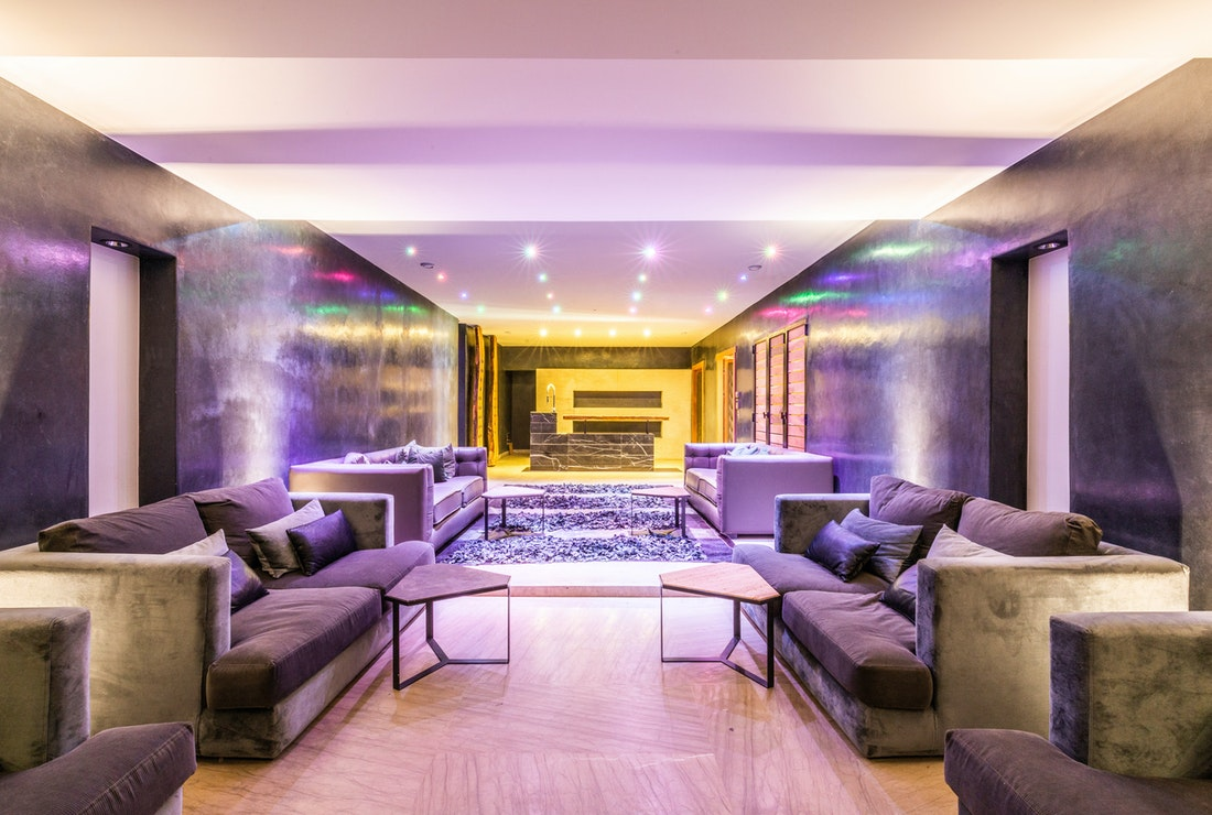 Lounge space with concrete walls and rainbow lights at Marhba luxury private villa in Marrakech