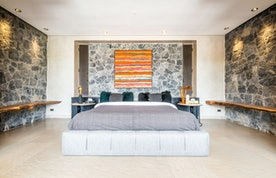 Bedroom with stone wall and real wood shelves at Marhba luxury private villa in Marrakech