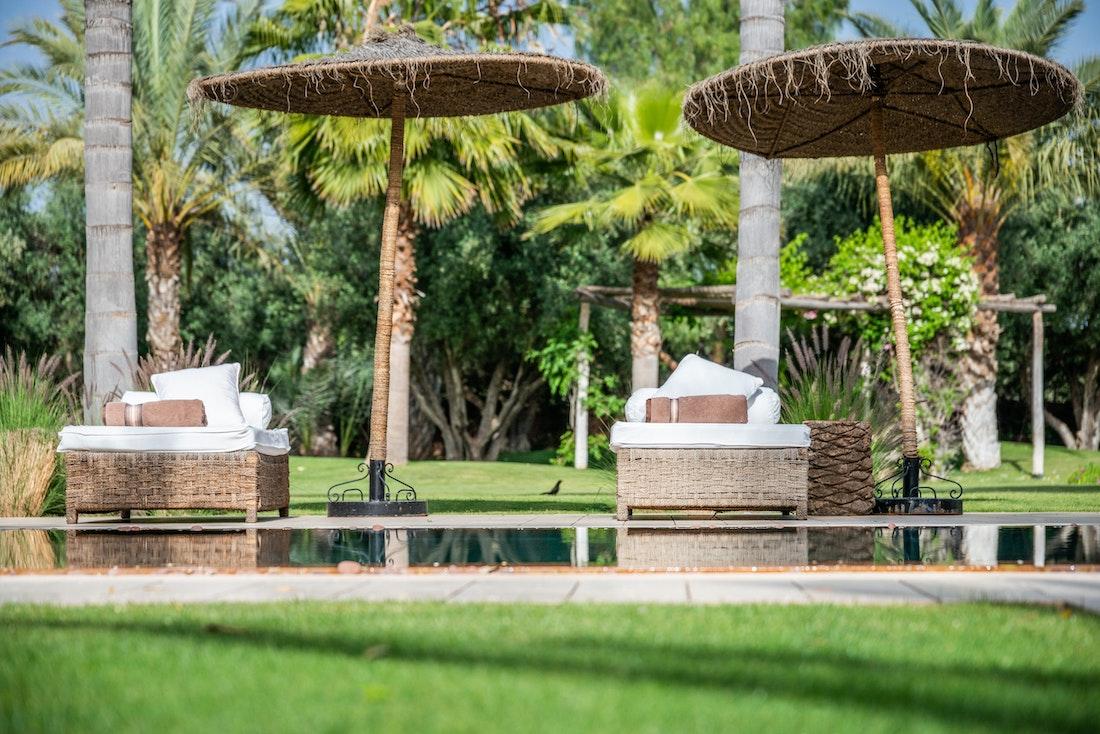 Raffia sunbeds near the pool of Zagora private villa in Marrakech