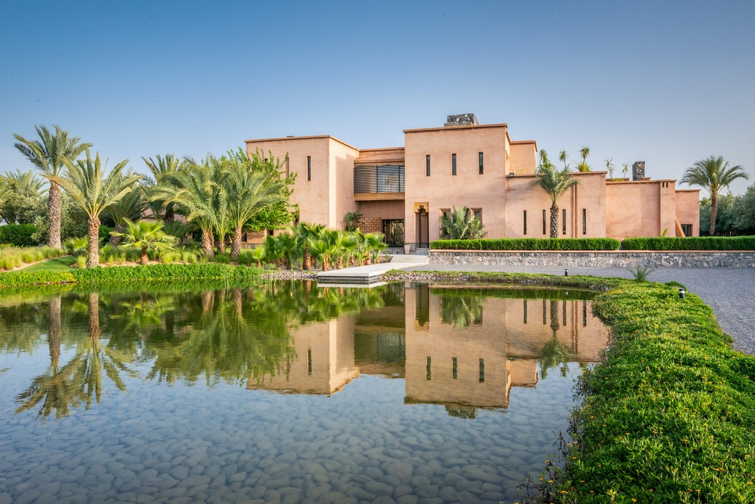 Private lake and garden with palm trees at Marhba luxury private villa in Marrakech