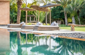 Private pool with raffia daybeds at Marhba luxury private villa in Marrakech