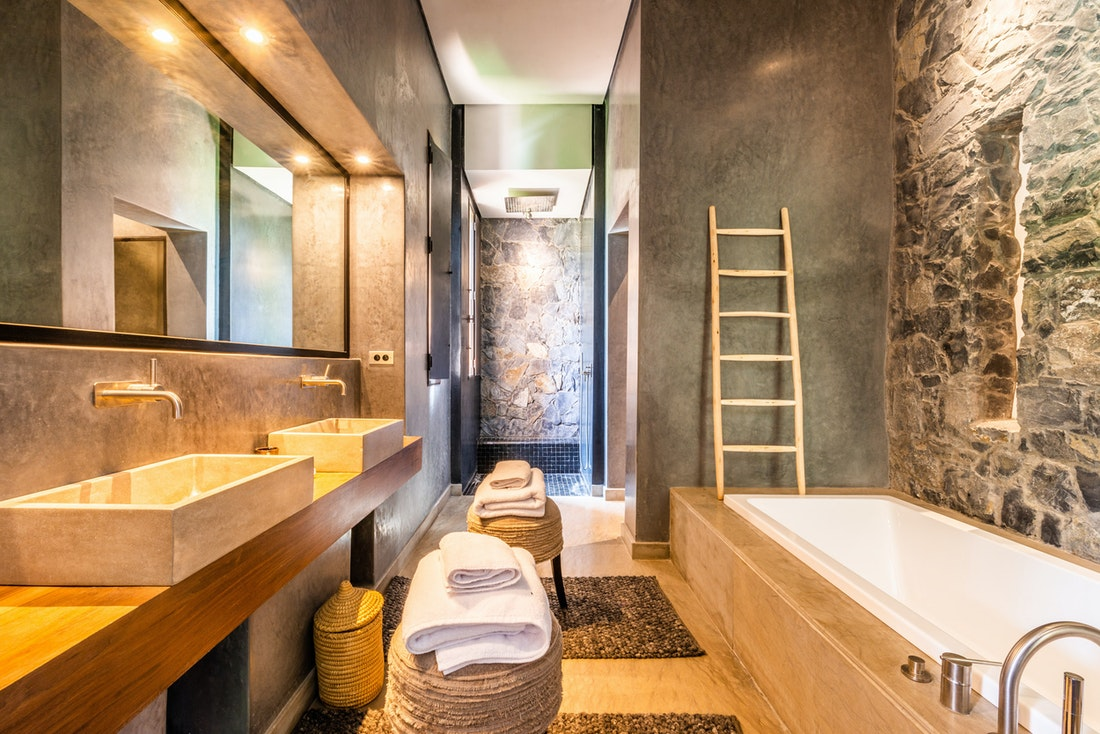 Ethnic and industrial style bathroom with concrete sinks and wooden bathroom furnitures at Marhba luxury private villa in Marrakech