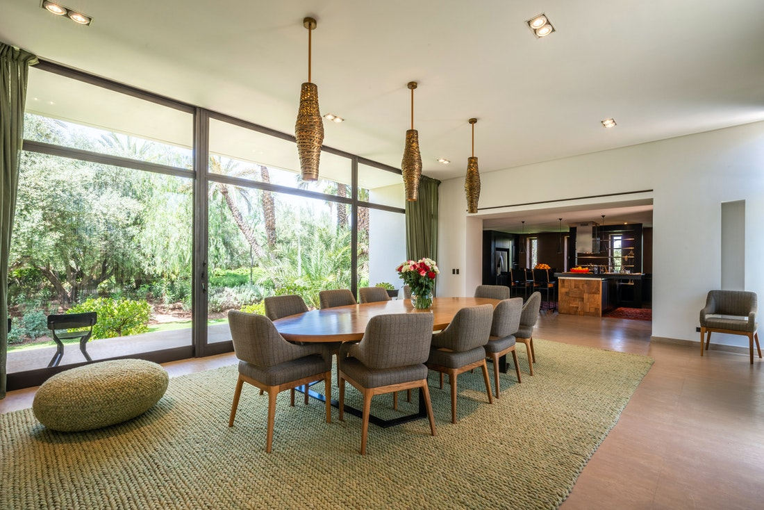Contemporary dining room with large knitted rug at Zagora private villa in Marrakech